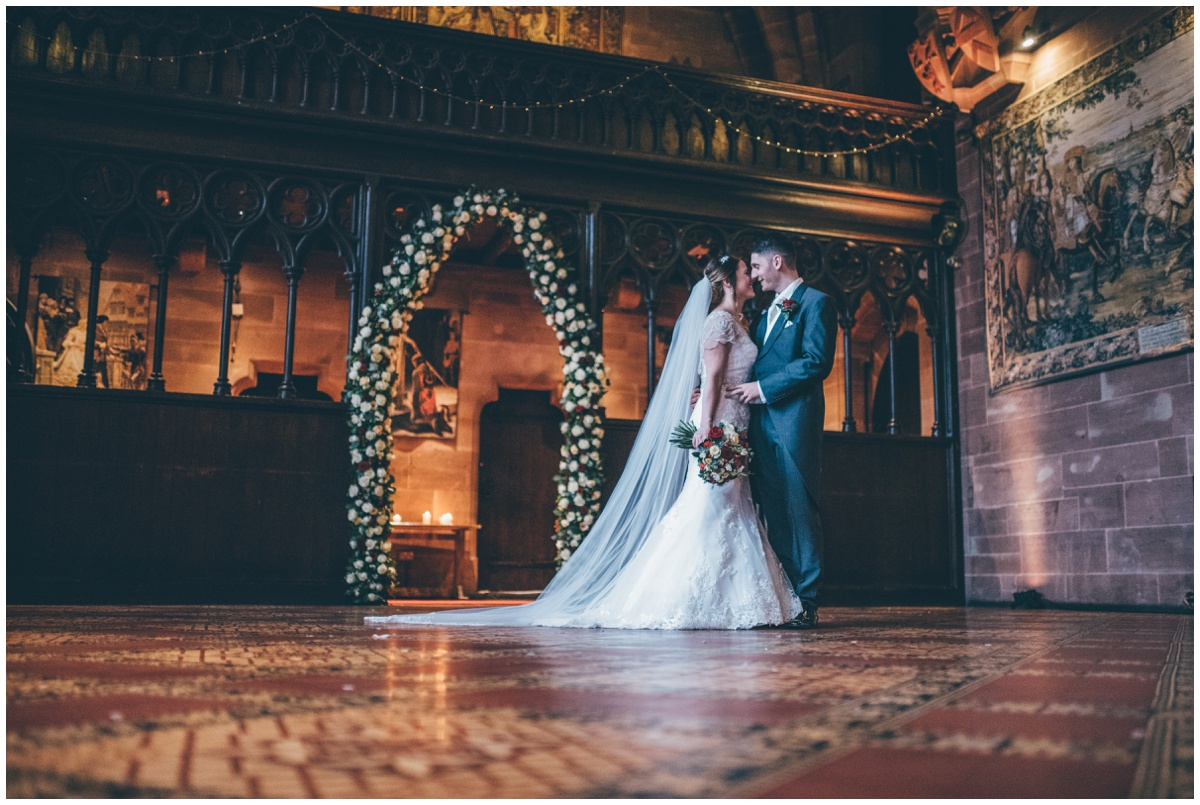 The new husband and wife have their wedding portraits taken in the Great Hall at Peckforton Castle.