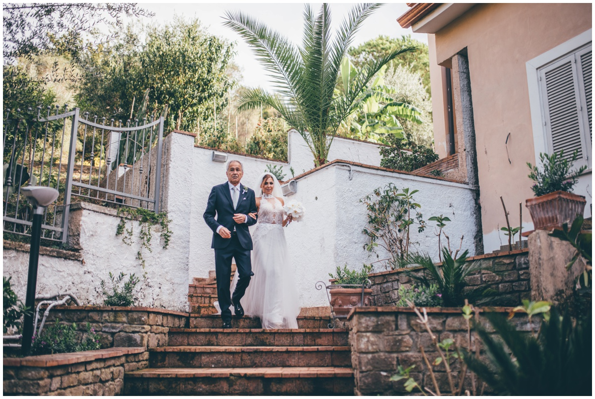 Stunning bride gets walked towards her guests by her father at Hotel Garden Riviera in Santa Maria Di Castellabate.