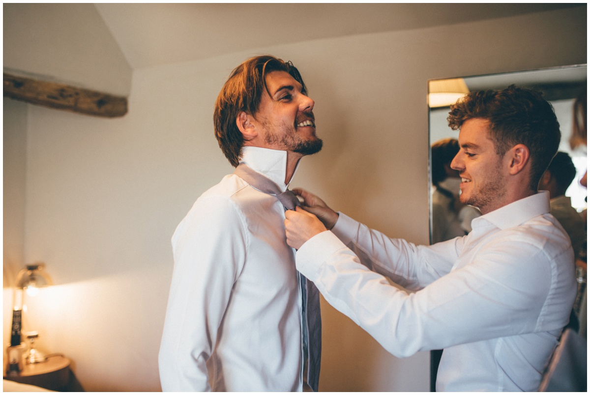Groomsman helps the groom with his tie.