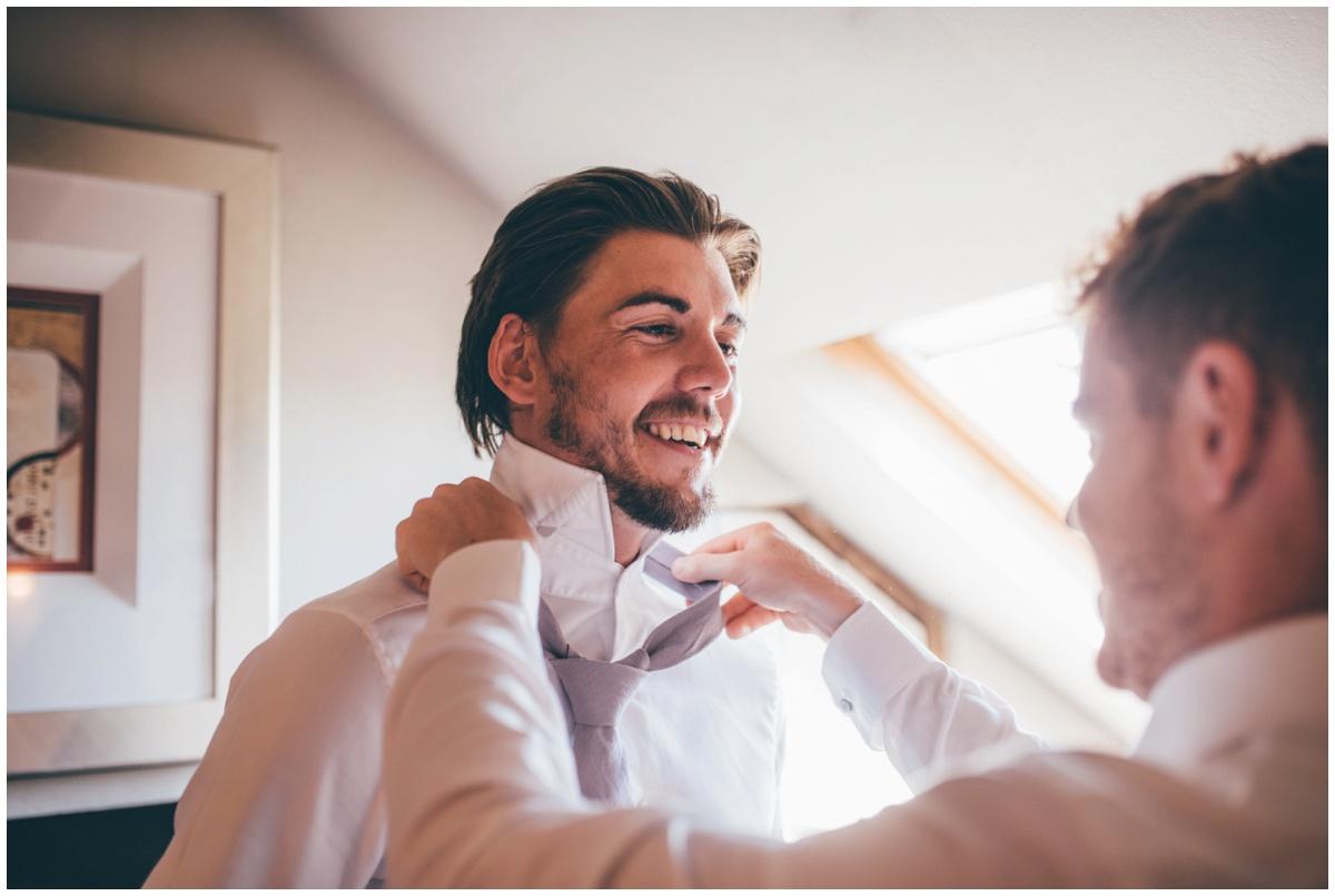 Groomsman helps groom with his tie.