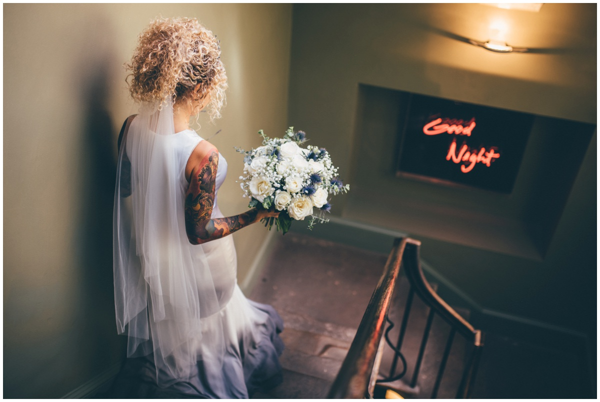 Beautiful tattooed bride walks down the stairs at Oddfellows in Chester.
