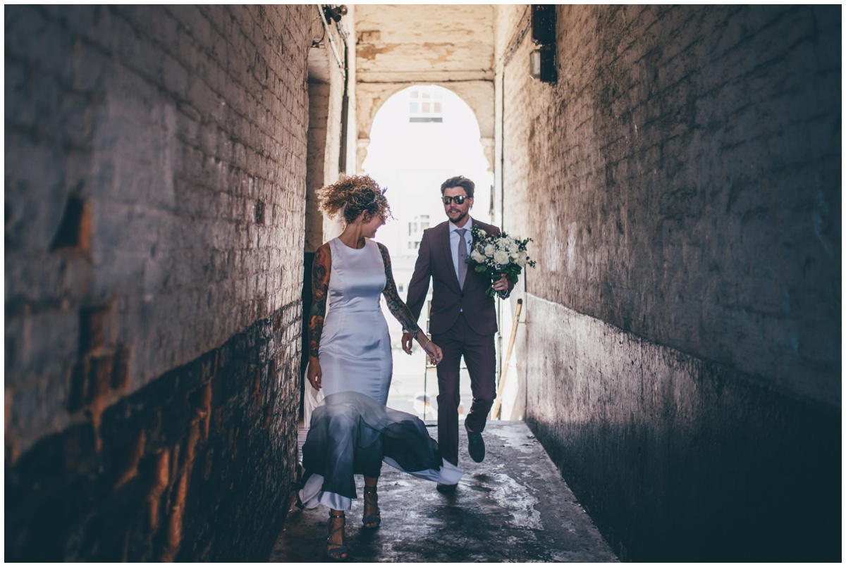 Cool and edgy bride and groom walk through an alleyway in Chester.