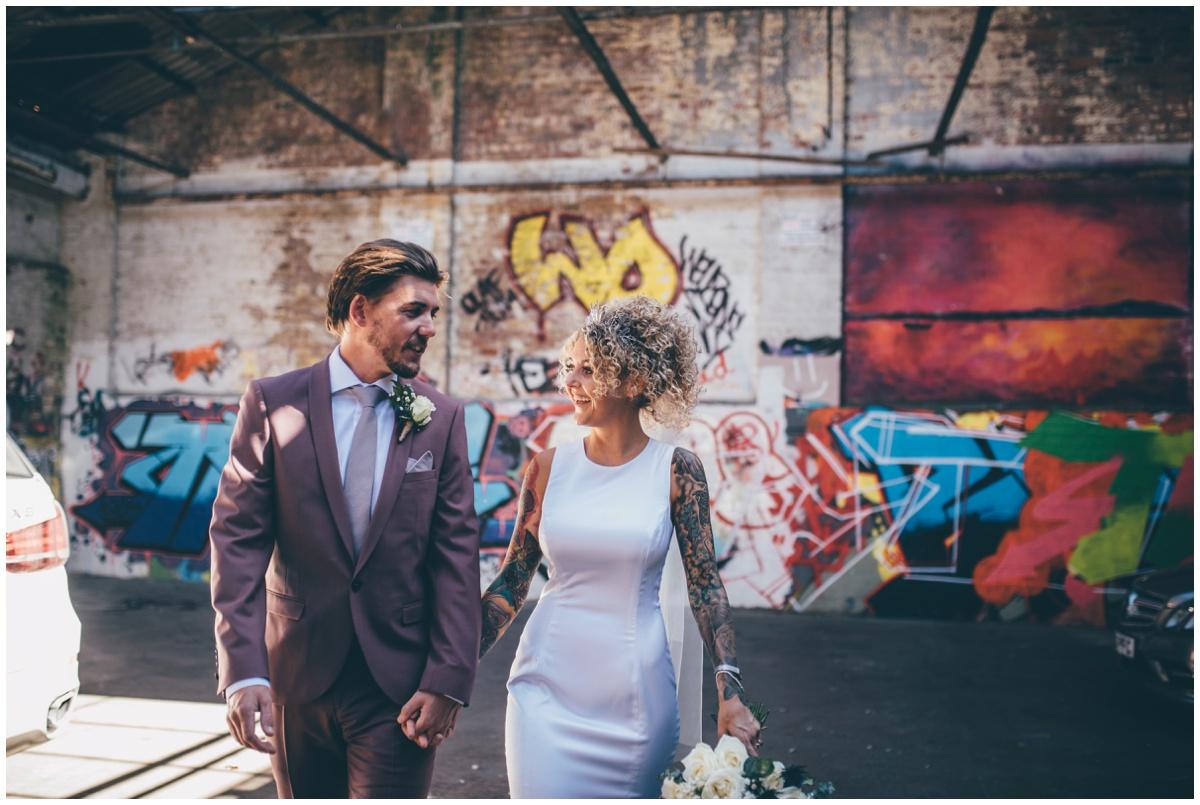 Tattooed bride in a brightly coloured graffiti filled car park.