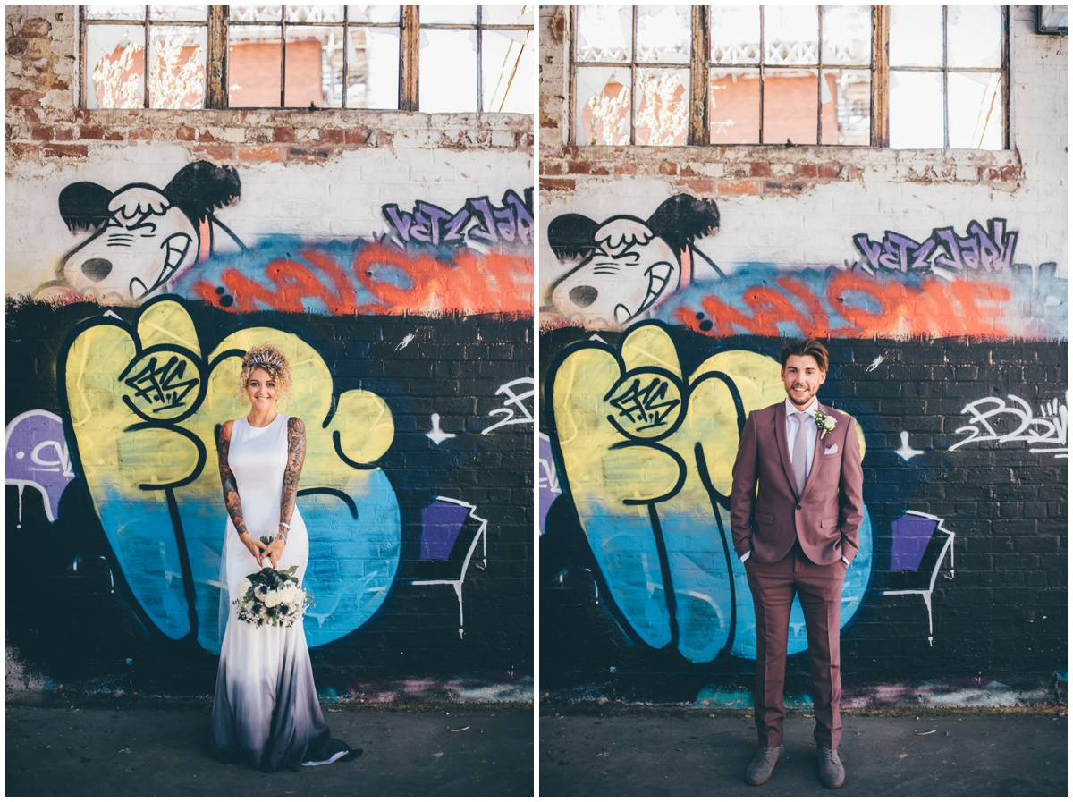 Bride and groom stand in brightly coloured graffiti car park.