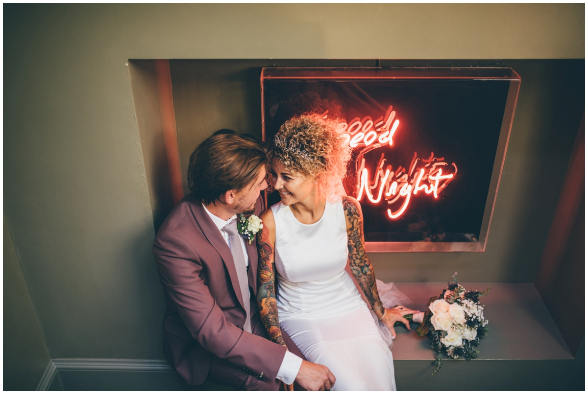 Bride and groom sit in front of bright neon lights in Oddfellows in Chester.