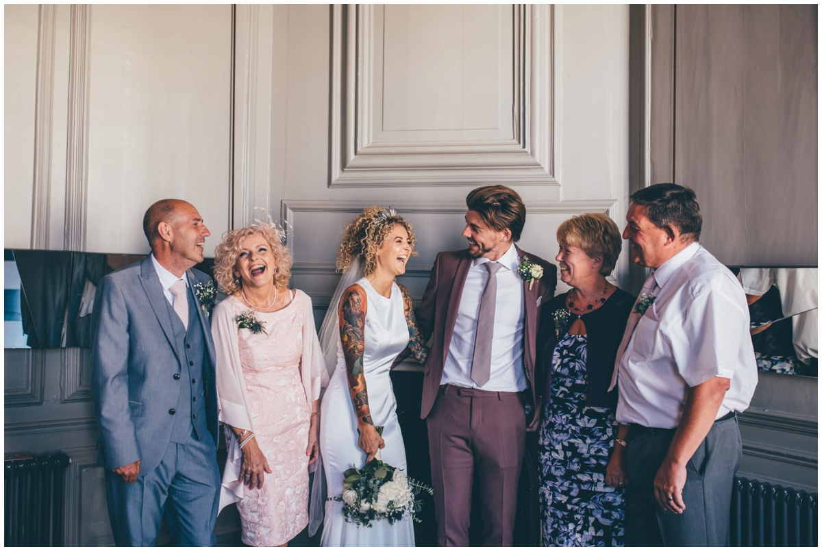 Tattooed Bride and her new husband in a pink suit laugh with their parents at Oddfellows in Chester.