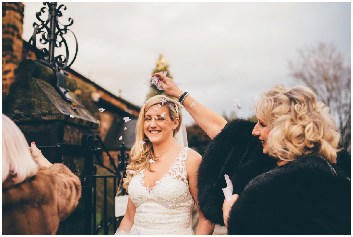 Guests pour confetti on New Years Eve bride in Cheshire.