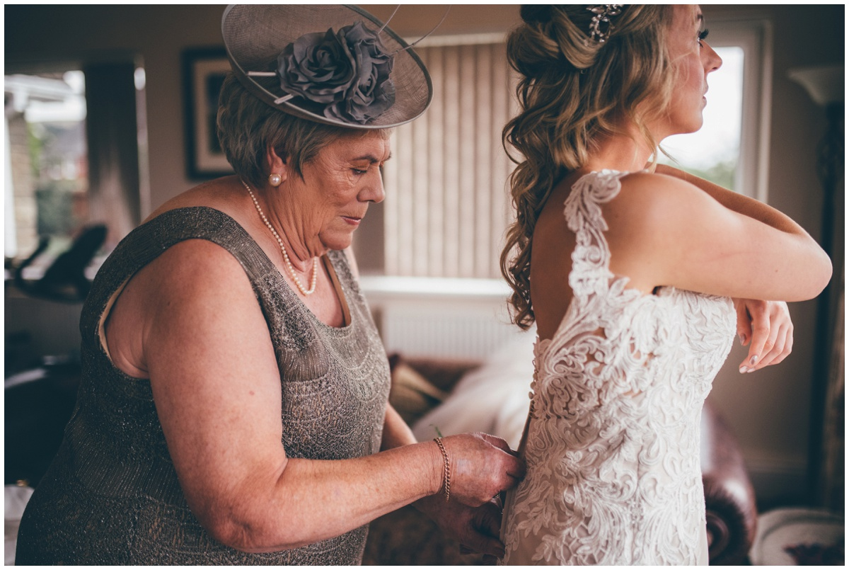 Bride's mum helps her into her wedding gown before her wedding in Staffordshire.