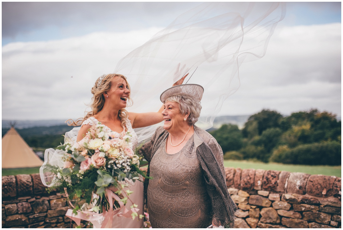 The wind blows the bride's beautiful veil whilst she's having her photograph taken with her mum.
