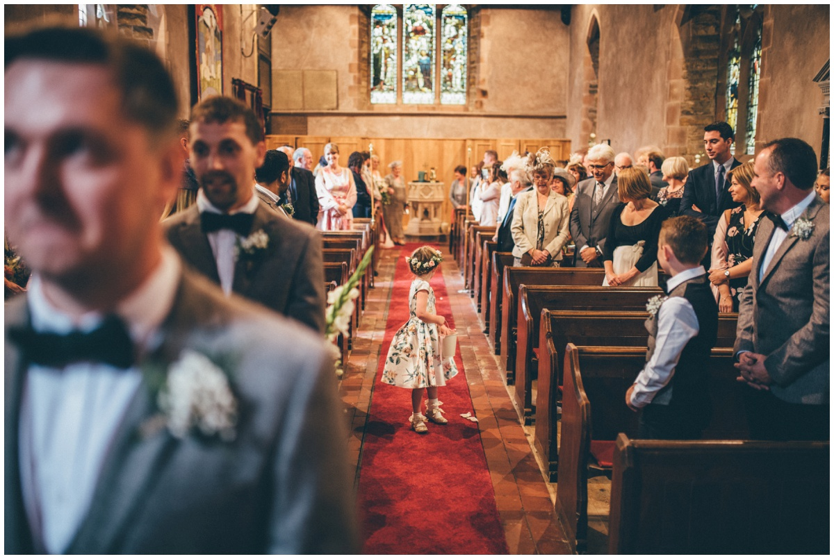 The adorable flower girl walks down the aisle ahead of the bride at St. Matthews church in Staffordshire.
