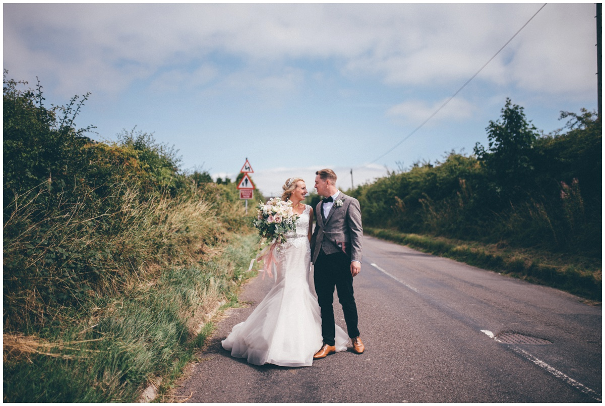 New husband and wife walk towards their blessing along a country road in Leek.