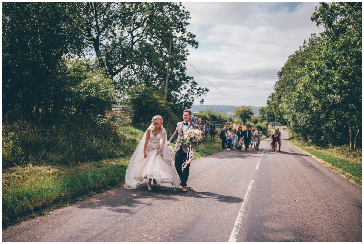 Bride and groom walk up the pretty country road, shot by Cheshire wedding photographer.