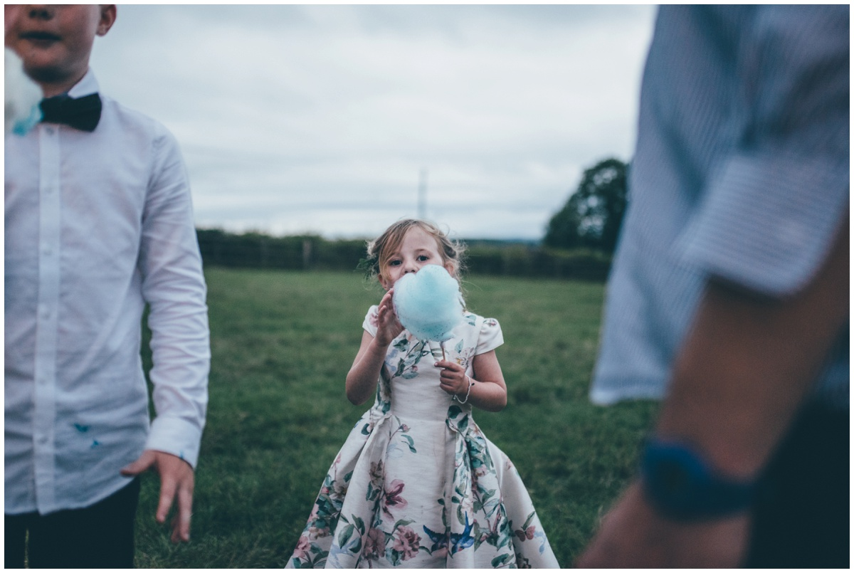 Cute flower girl enjoys candyfloss at a tipi wedding in Leek, Staffordshire.