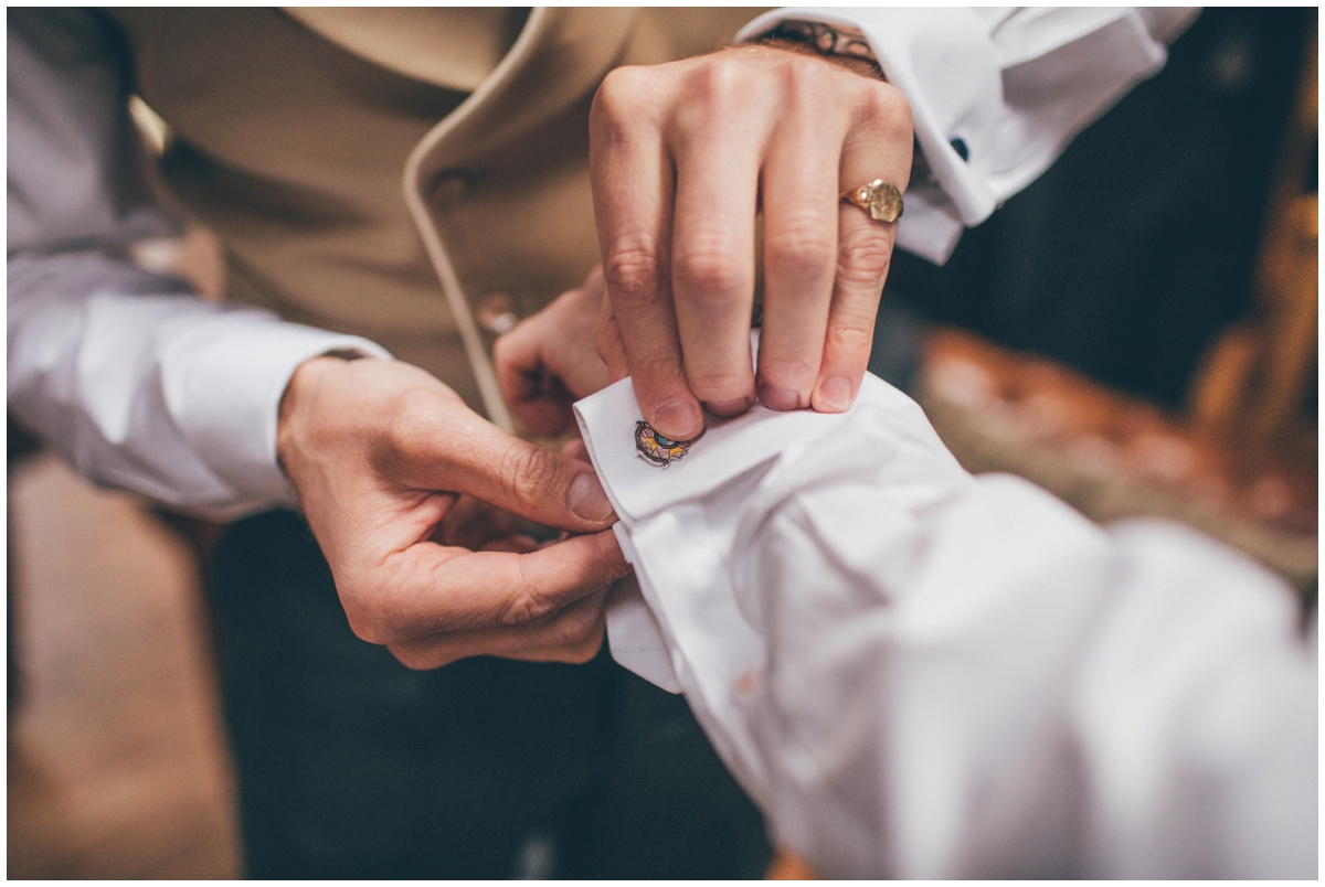 Groomsmen helps the groom fasten his army cufflinks.