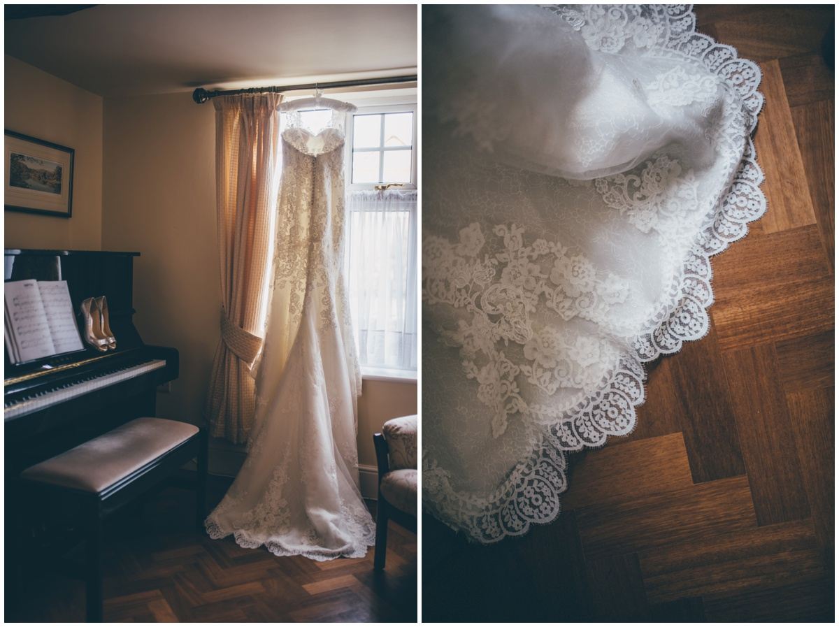 Stunning lace wedding gown hung up.