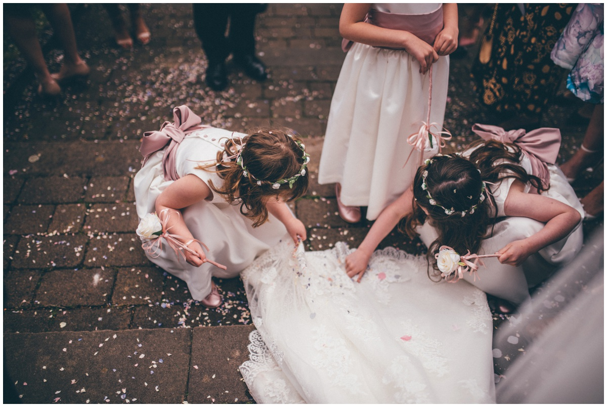 The flower girls pick confetti off the bride's beautiful lace train.