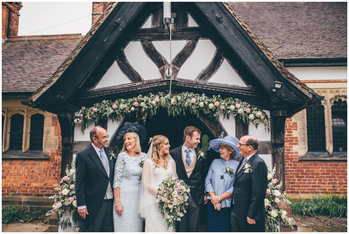 The newlyweds pose with their in-laws outside St Mary's Church in Cheshire.