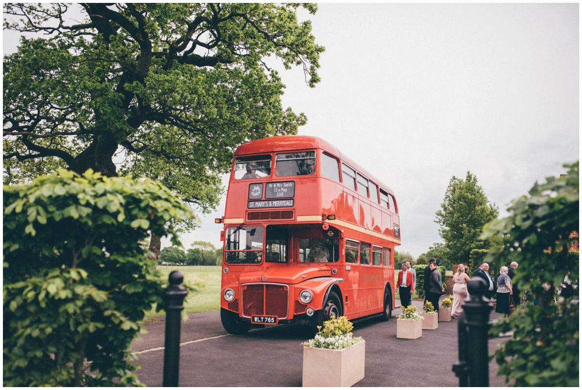 The guests arrive to the wedding at Merrydale Manor in a double decker red bus.