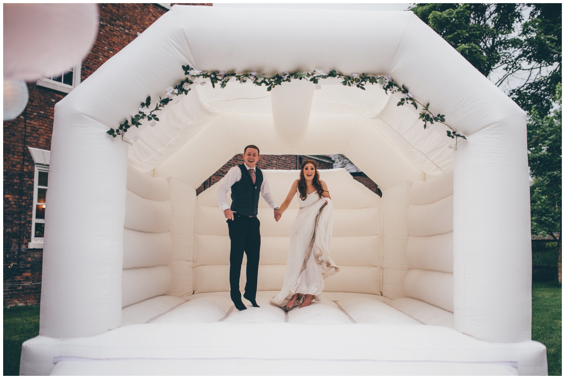 Bride and Groom have fun bouncing on their wedding bouncey castle at Trafford Hall.