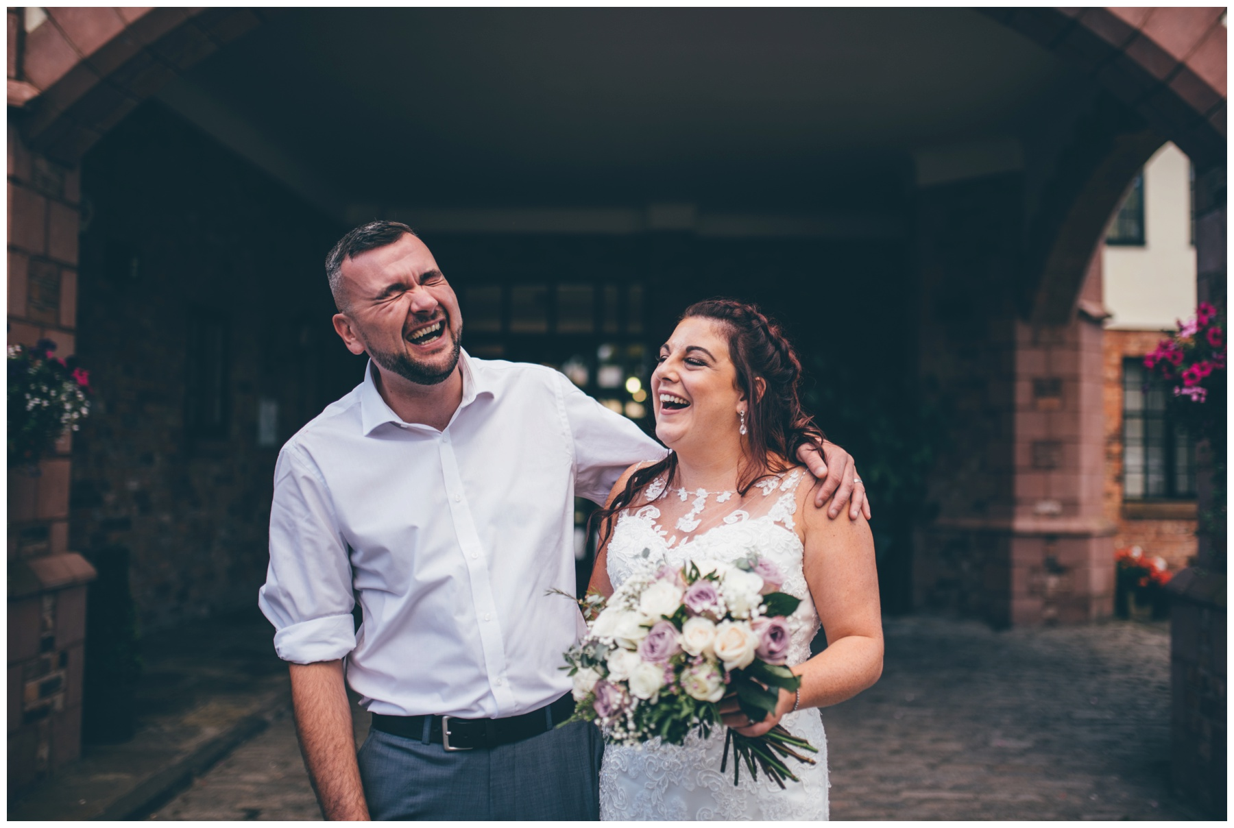Bride and Groom crack up laughing together after their wedding at Crabwall Manor just outside Chester in Cheshire.