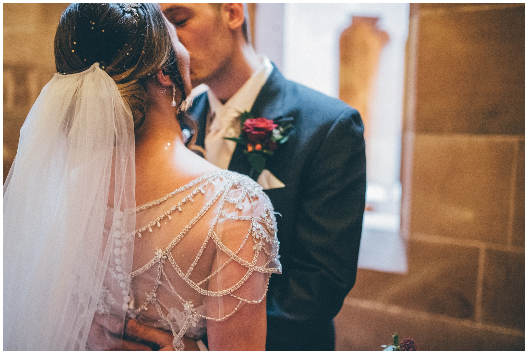 Details of brides beaded wedding gown as she kisses her groom at Peckforton Castle in Cheshire.