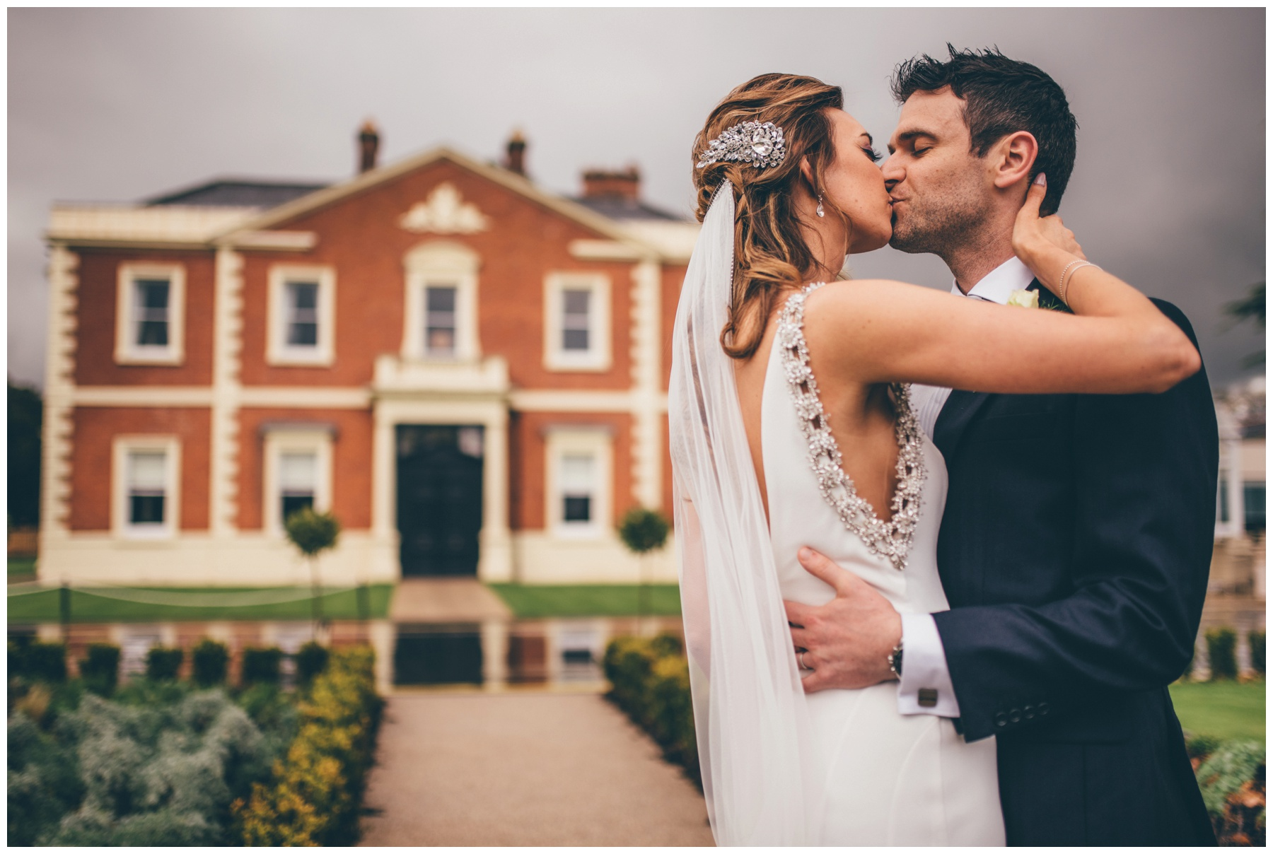 Bride and groom kiss in front of their wedding venue in Hoole, Chester. The Doubletree by Hilton in Cheshire.