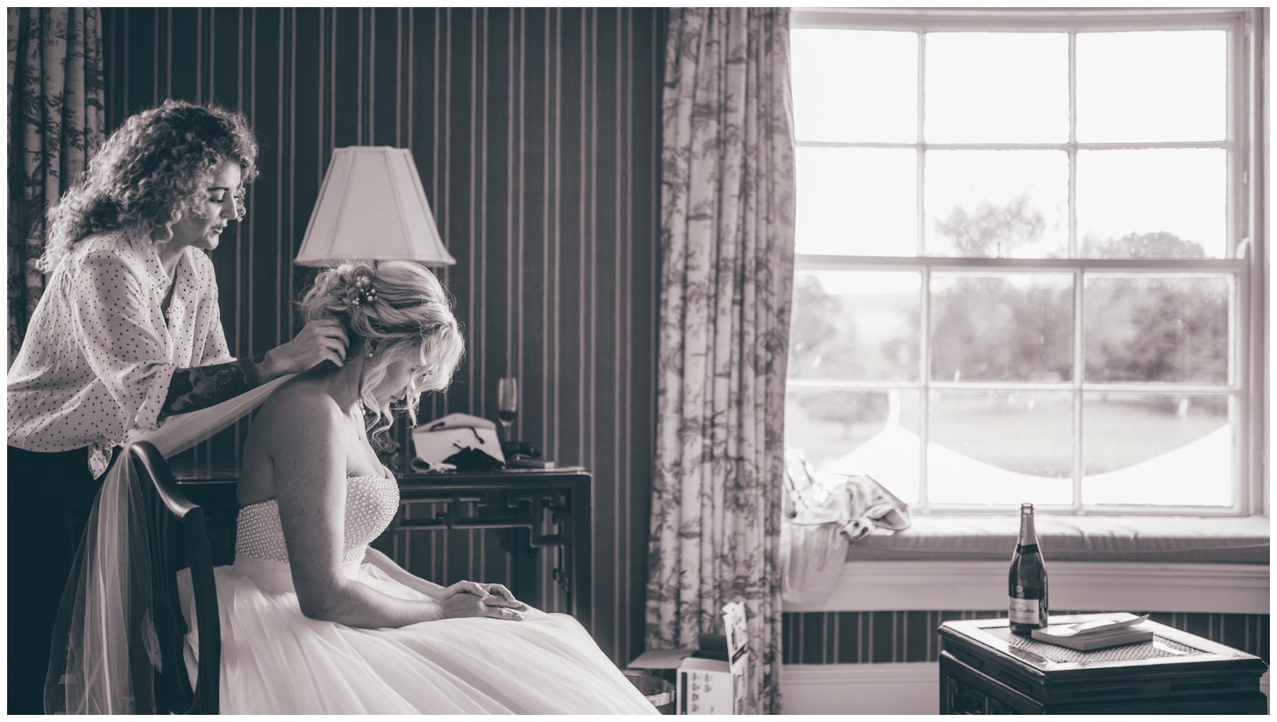 Wedding hairdresser puts the brides veil in and completes finishing touches on the beautiful bride at the Swinton Park Estate in Yorkshire.
