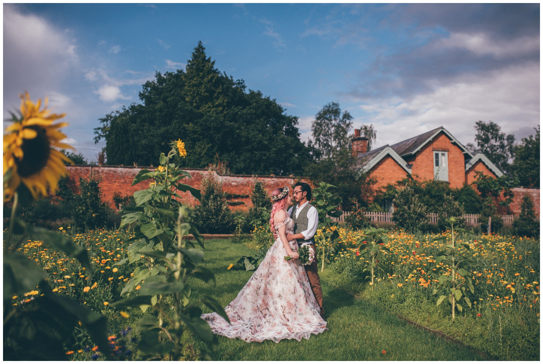 Bride in stunning floral Berketex wedding gown with her husband at Sugnall Walled Gardens in Staffordshire.