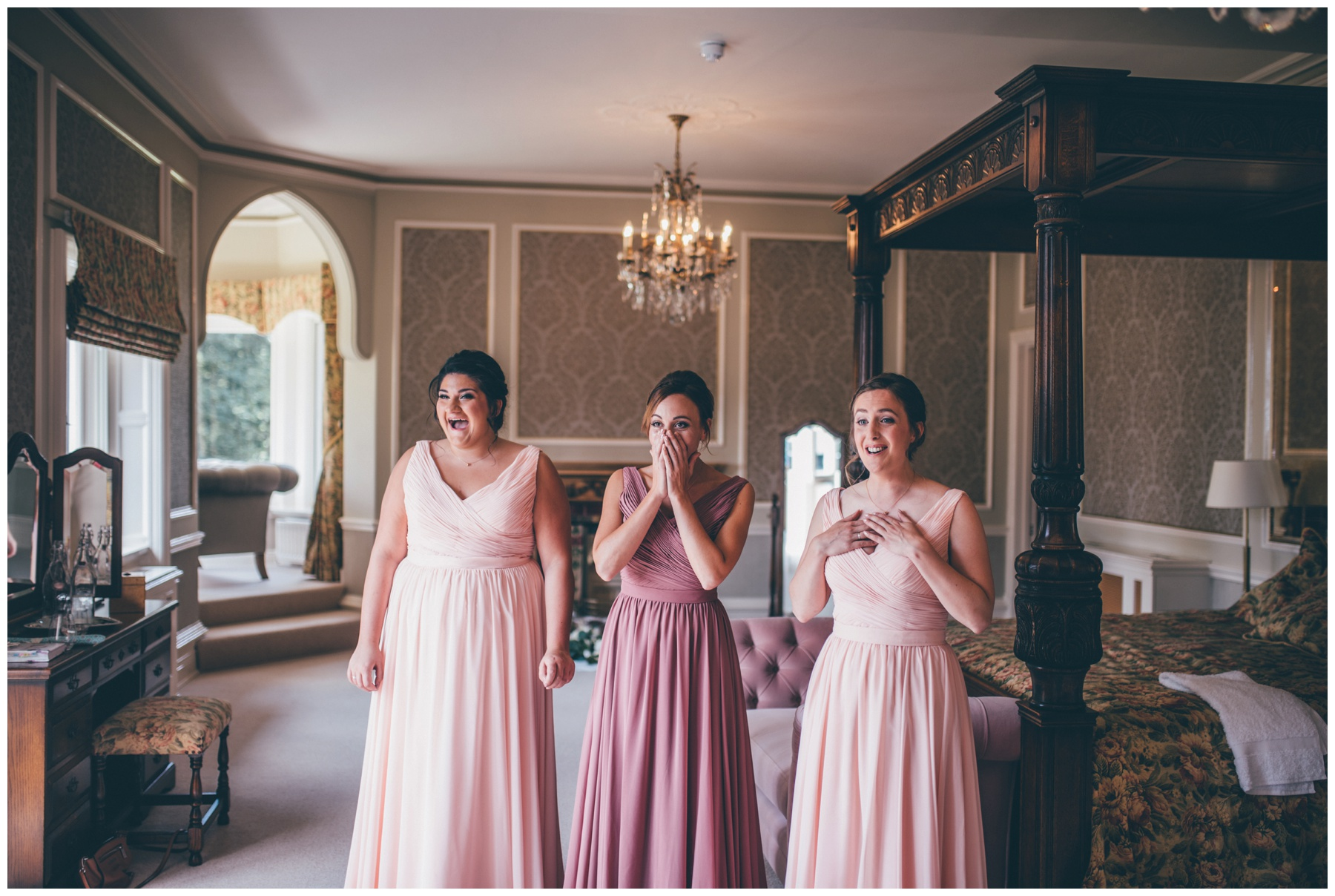 Bridesmaids reaction to seeing the bride in her dress for the first time at Tilstone House in Cheshire.