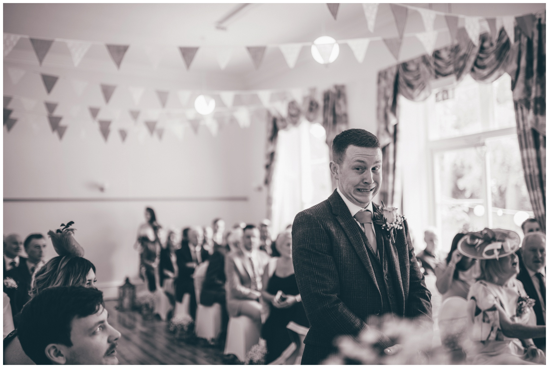 Groom waits nervously for his bride to walk down the aisle at Trafford Hall.