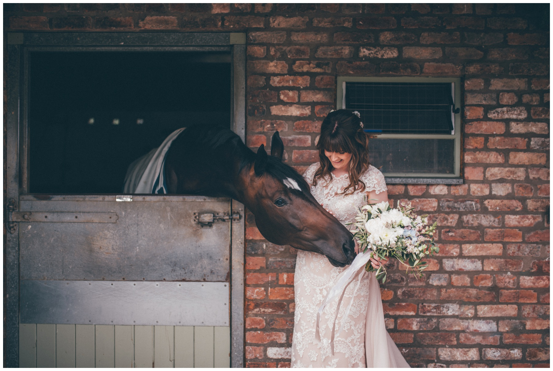 Bride strokes a horse at the Holford Estate wedding venue.
