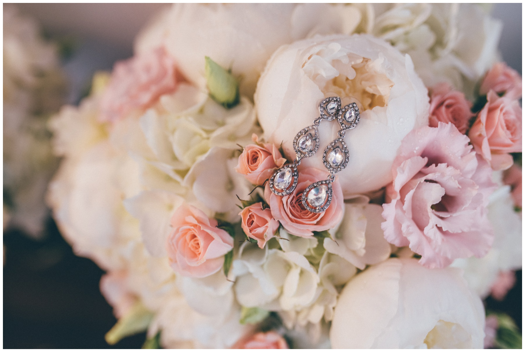 Brides stunning diamond earring against her beautiful wedding bouquet of peonies.