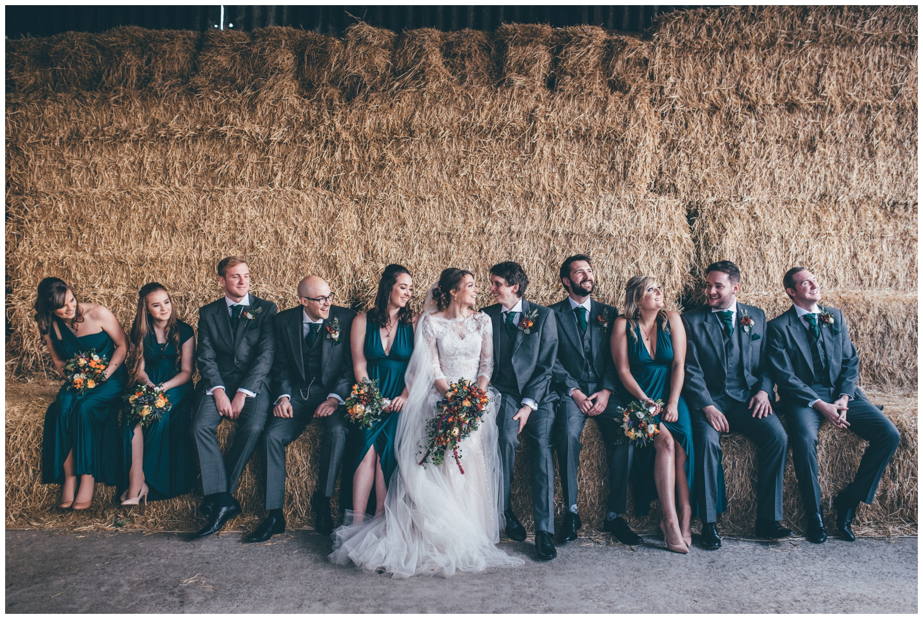 Bridal party all on hay bales together at Owen House wedding barn, new wedding venue in Cheshire.