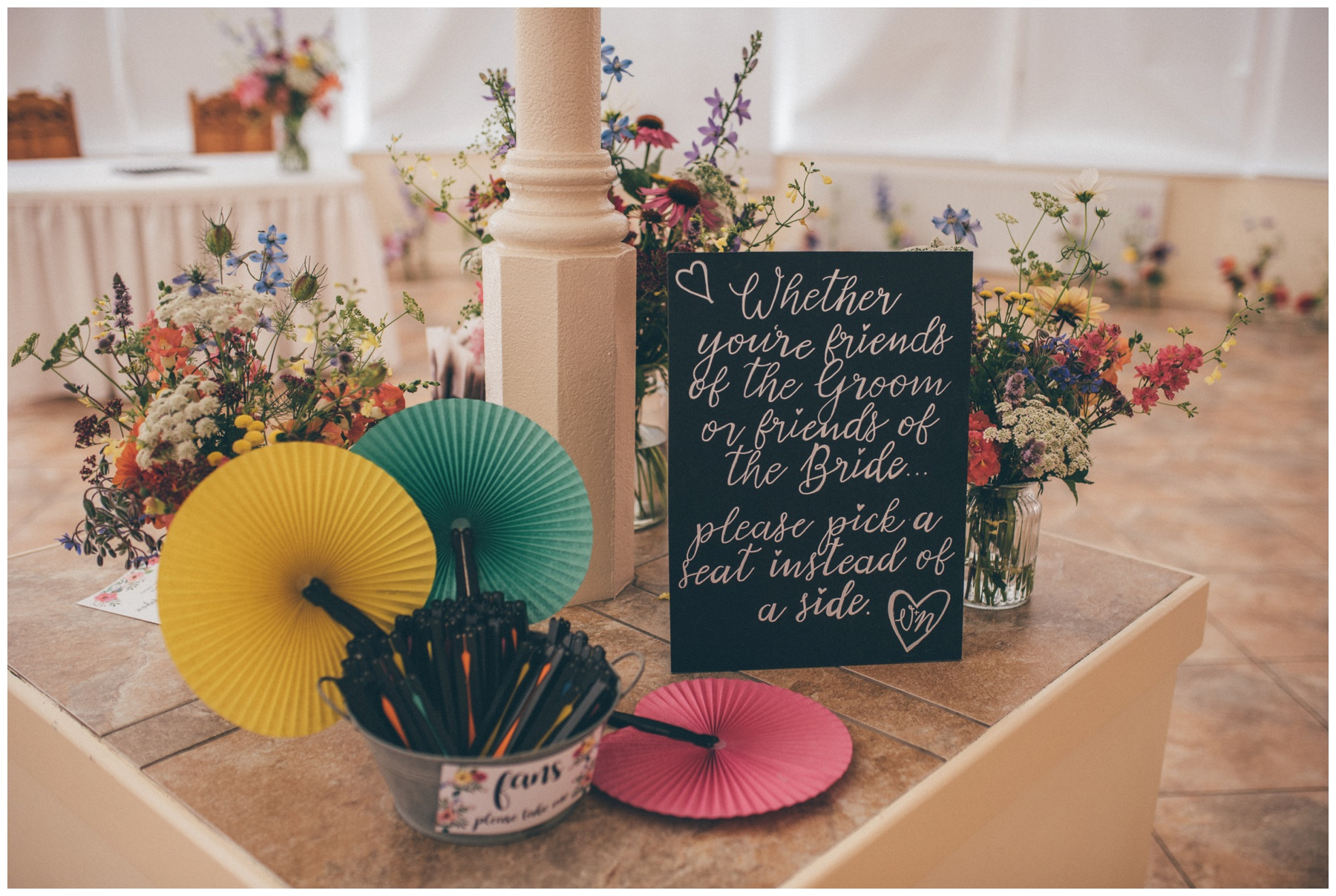 Bright coloured flowers and fans for a summer wedding at Combermere Abbey.