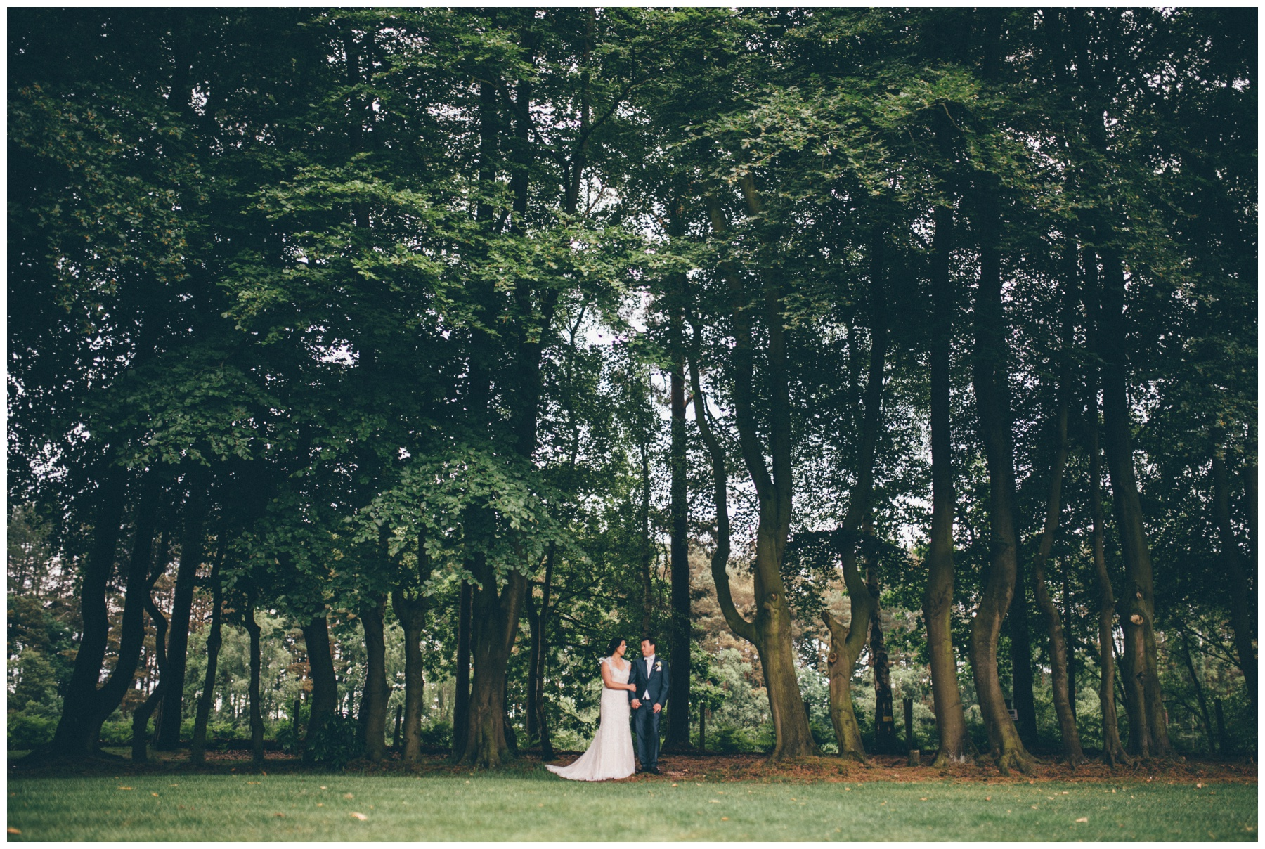 Bride and groom stand amongst the trees at Nunsmere Hall in Cheshire.