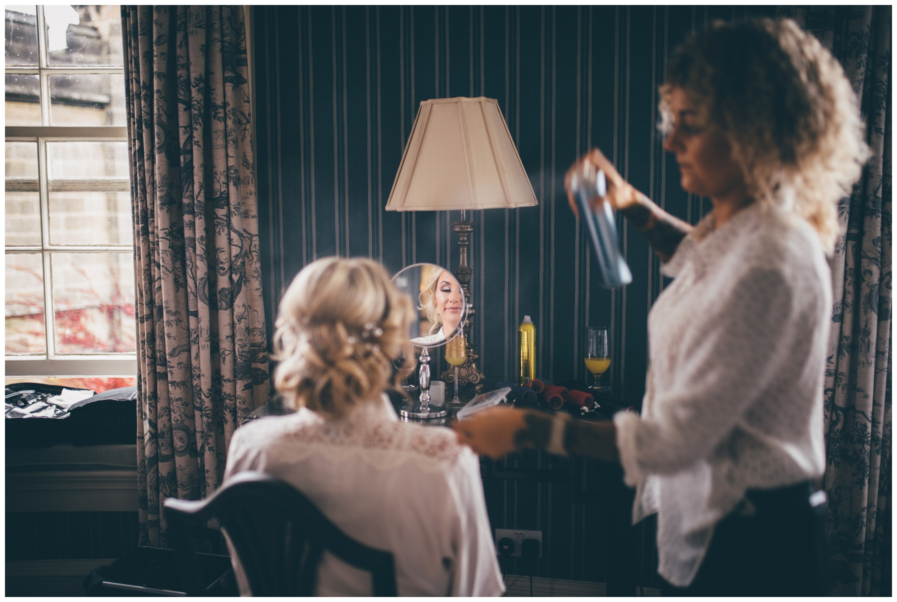 Stunning bridal reflection as the hairdresser does her hair on the wedding morning at Swinton Park Estate in Yorkshire.