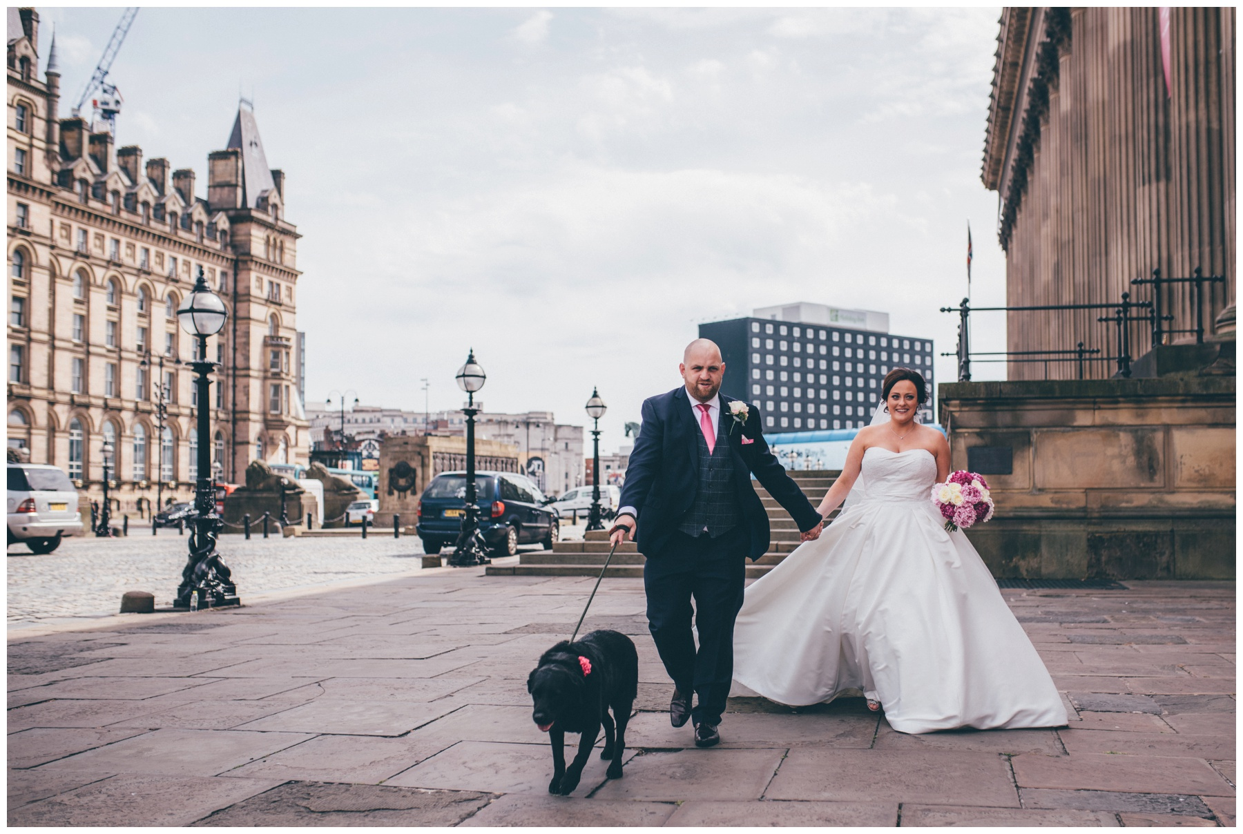 Bride and groom walk through Liverpool City Centre with their dog after their ceremony at St George's Hall.