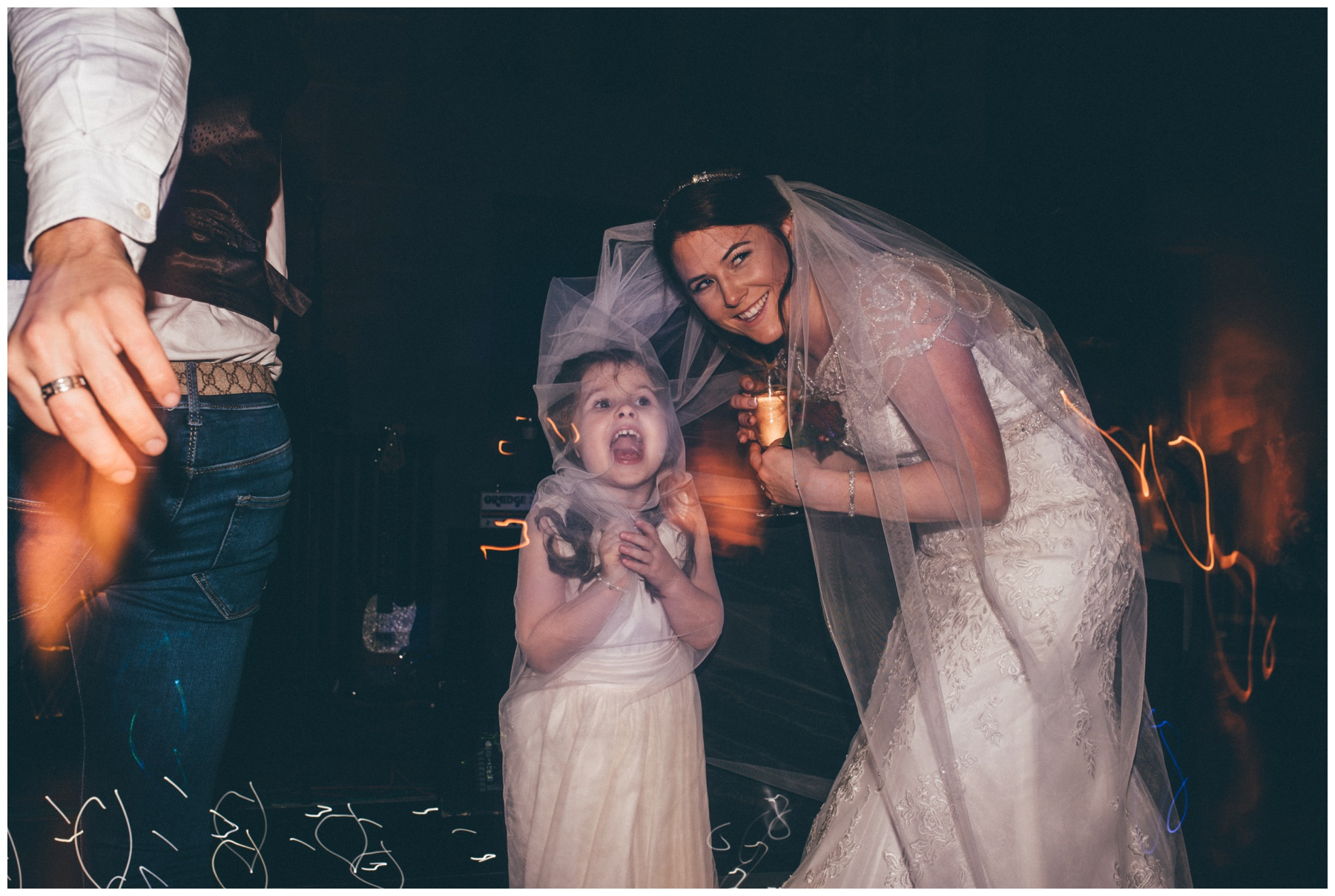 Cute flower girl and the bride both hide under the veil at Peckforton Castle in Cheshire.