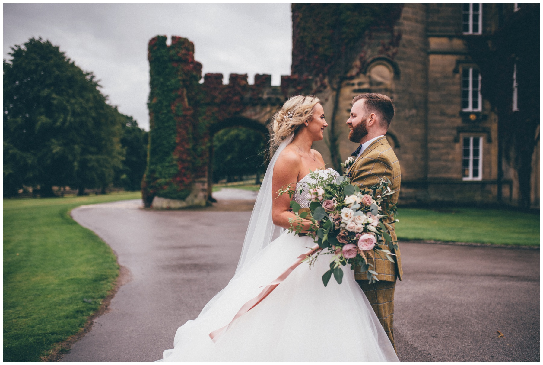 Bride and groom cuddle outside their gorgeous Yorkshire wedding venue, Swinton Park Estate.