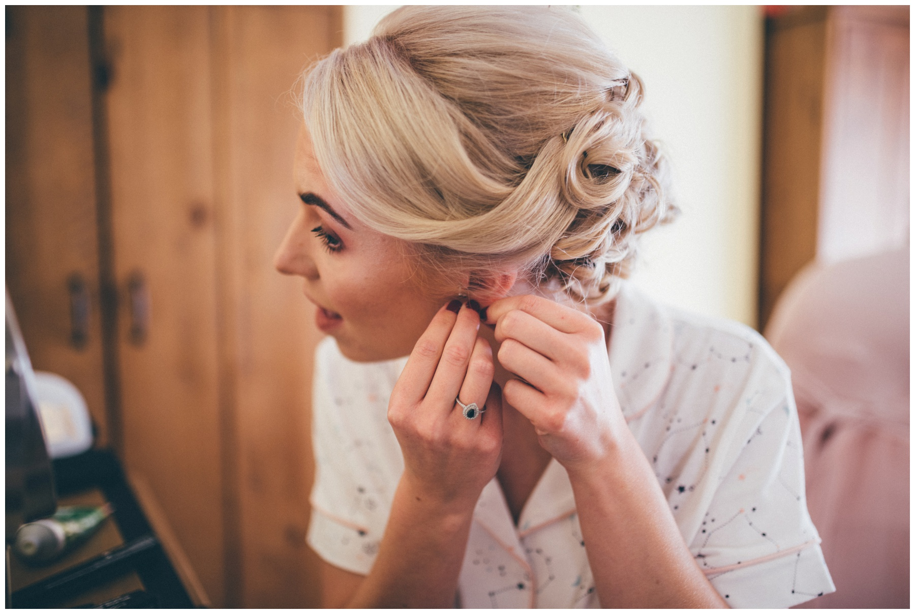 Bride puts on her sapphire and diamond earrings.