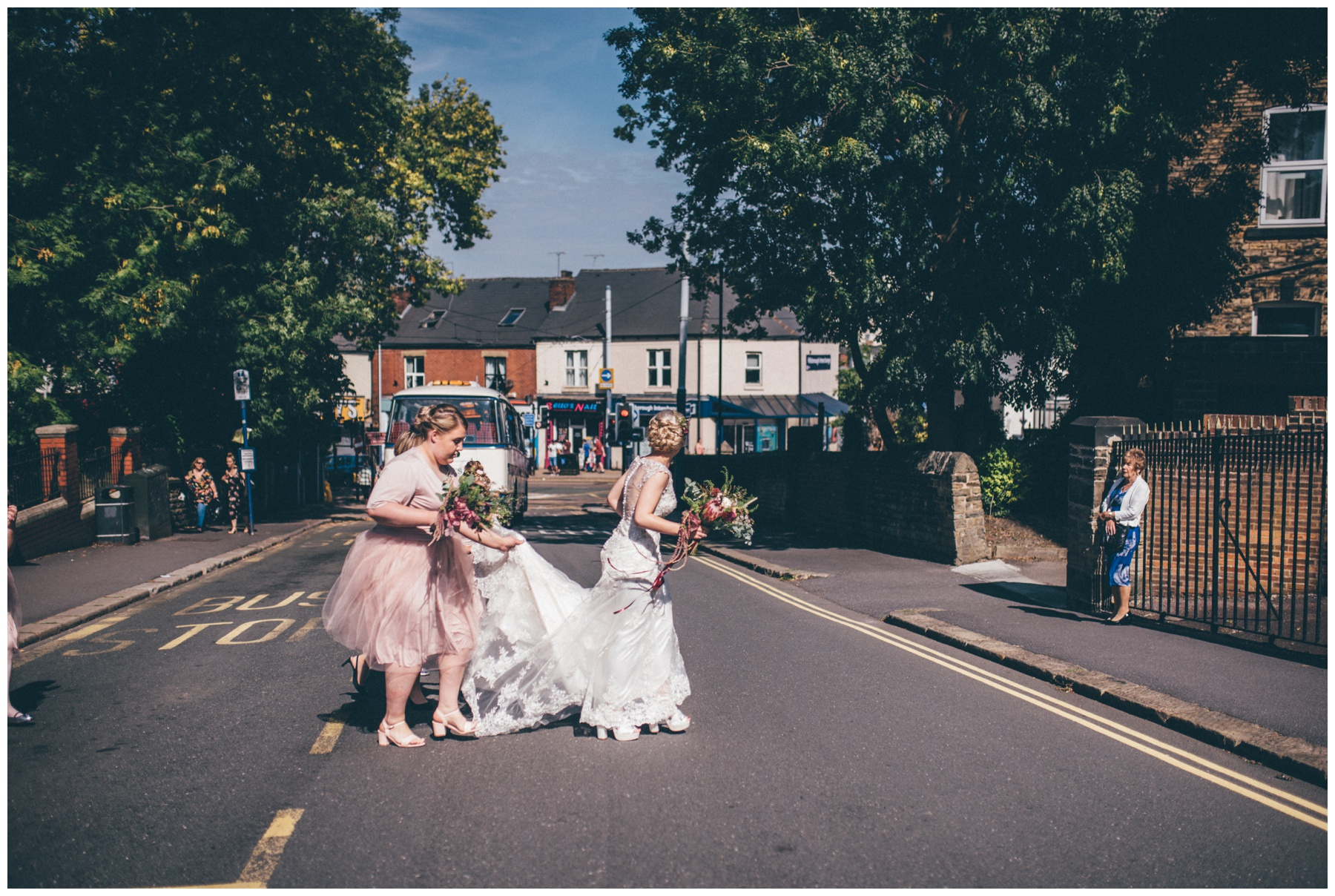 Bride gets helped across the busy city road by her bridesmaids.
