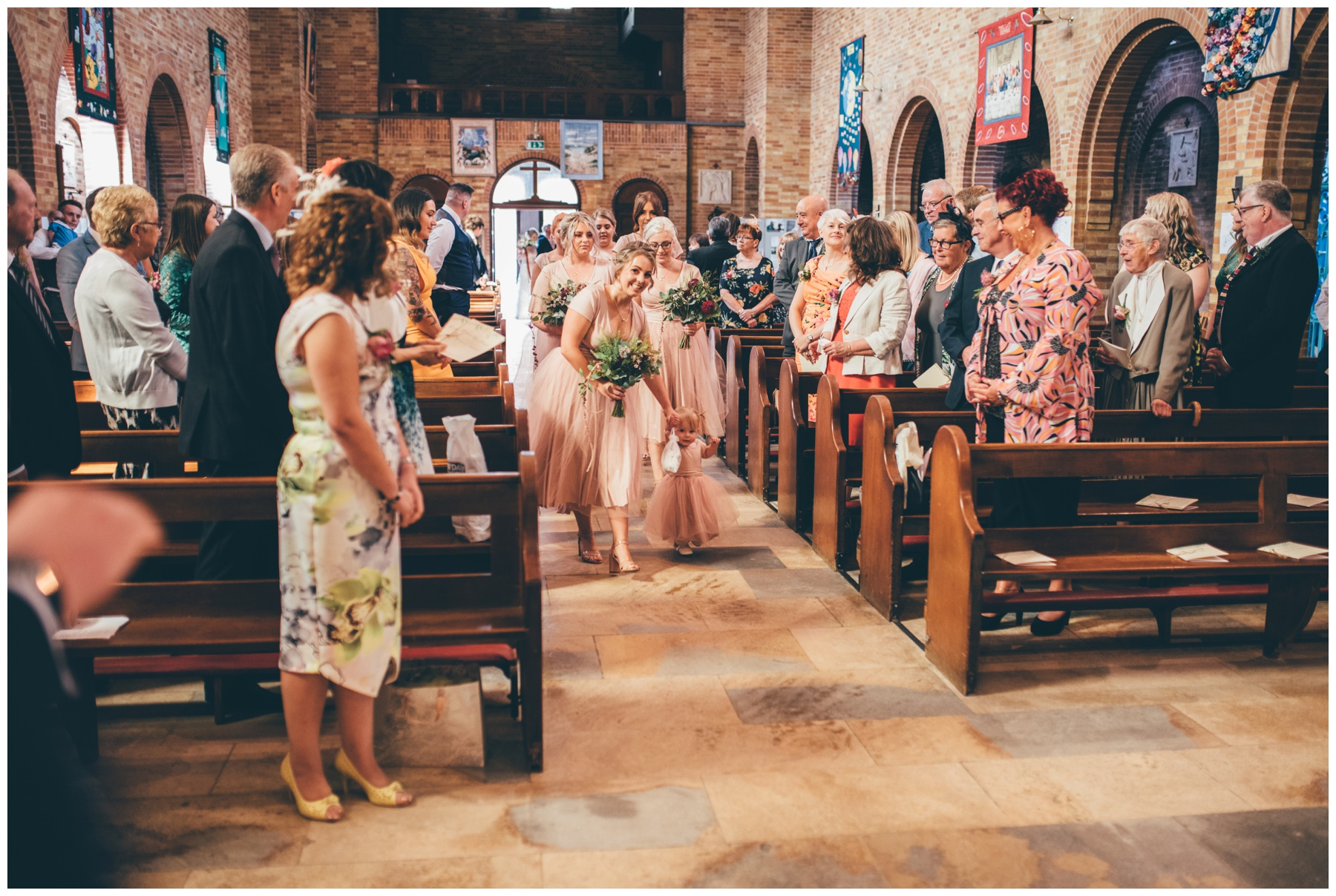 Bridesmaids make their way down the aisle at Sacred Heart in Sheffield.