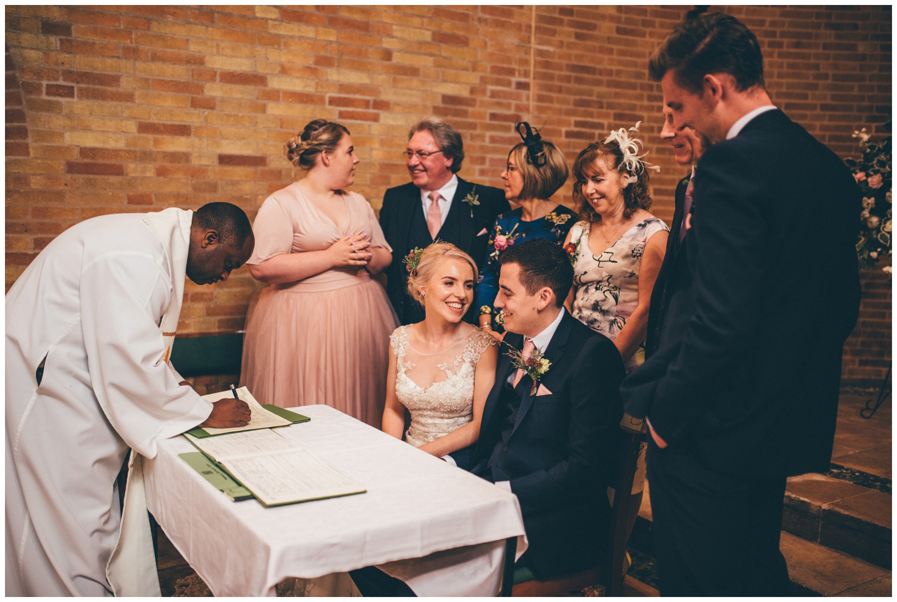 Bride and groom share a joke during the signing of their register at Sacred Heart church in Sheffield.