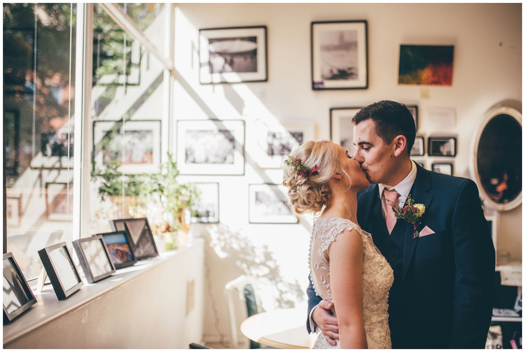 Bride and groom share a kiss in the art gallery of The Hide in Sheffield city centre wedding.