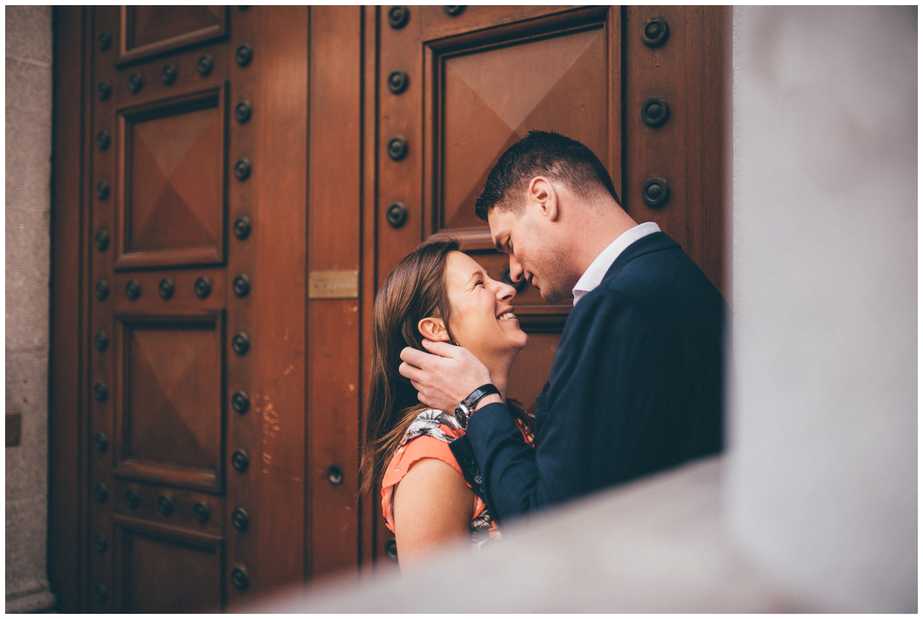 Couple kiss in a doorway during their engagement shoot in London city centre.