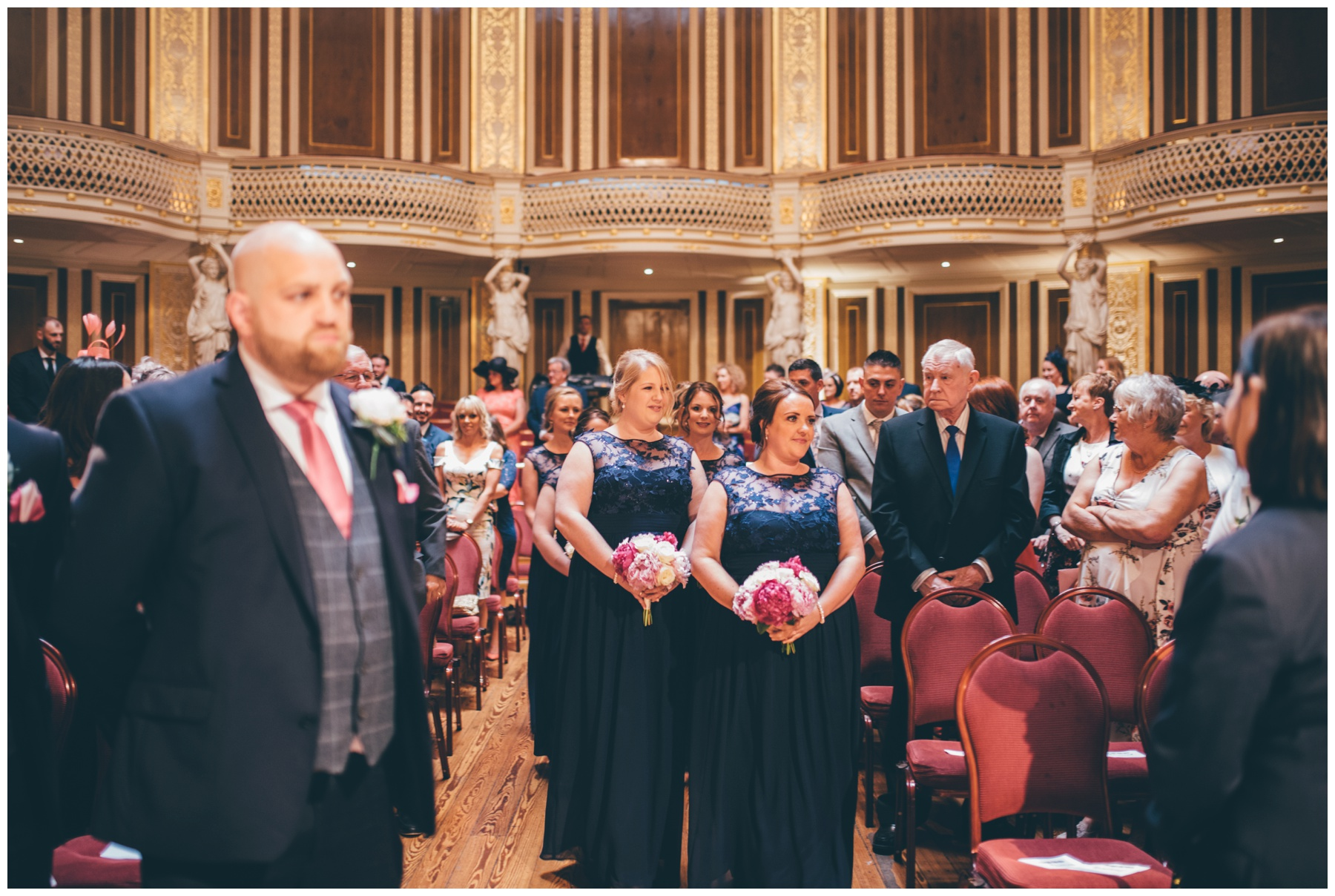 Bridesmaids walk down the aisle at St Georges Hall wedding in Liverpool City Centre.