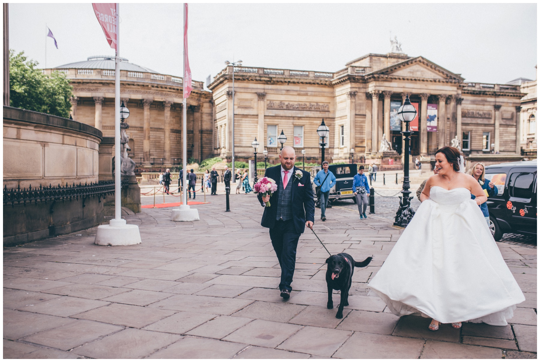 New husband and wife walk their dog in Liverpool city centre just after their wedding.