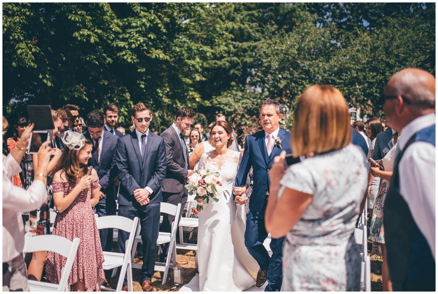 Bride walks down the aisle with her Dad at her outdoor wedding ceremony at Tilstone House.