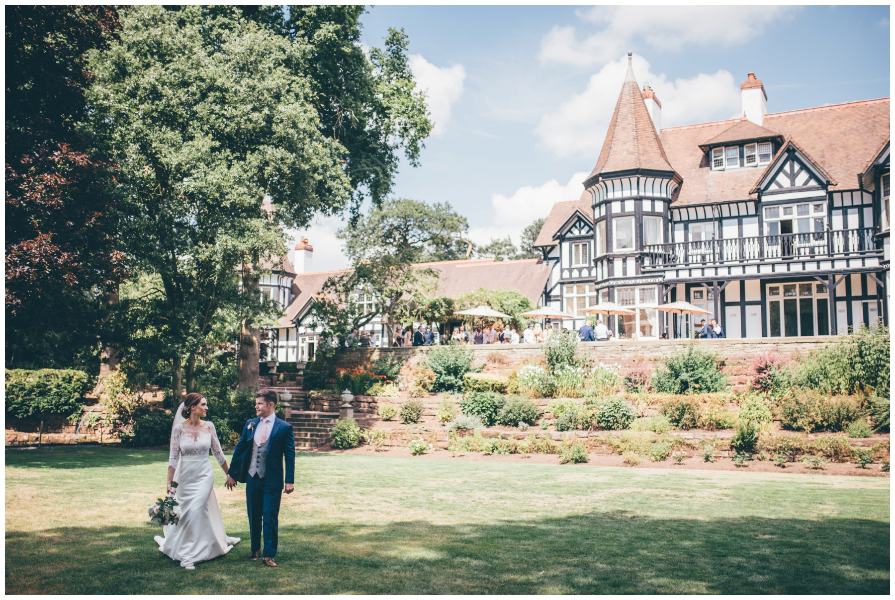 Newlyweds stroll across the beautiful grounds at Tilstone House in Tarporley.