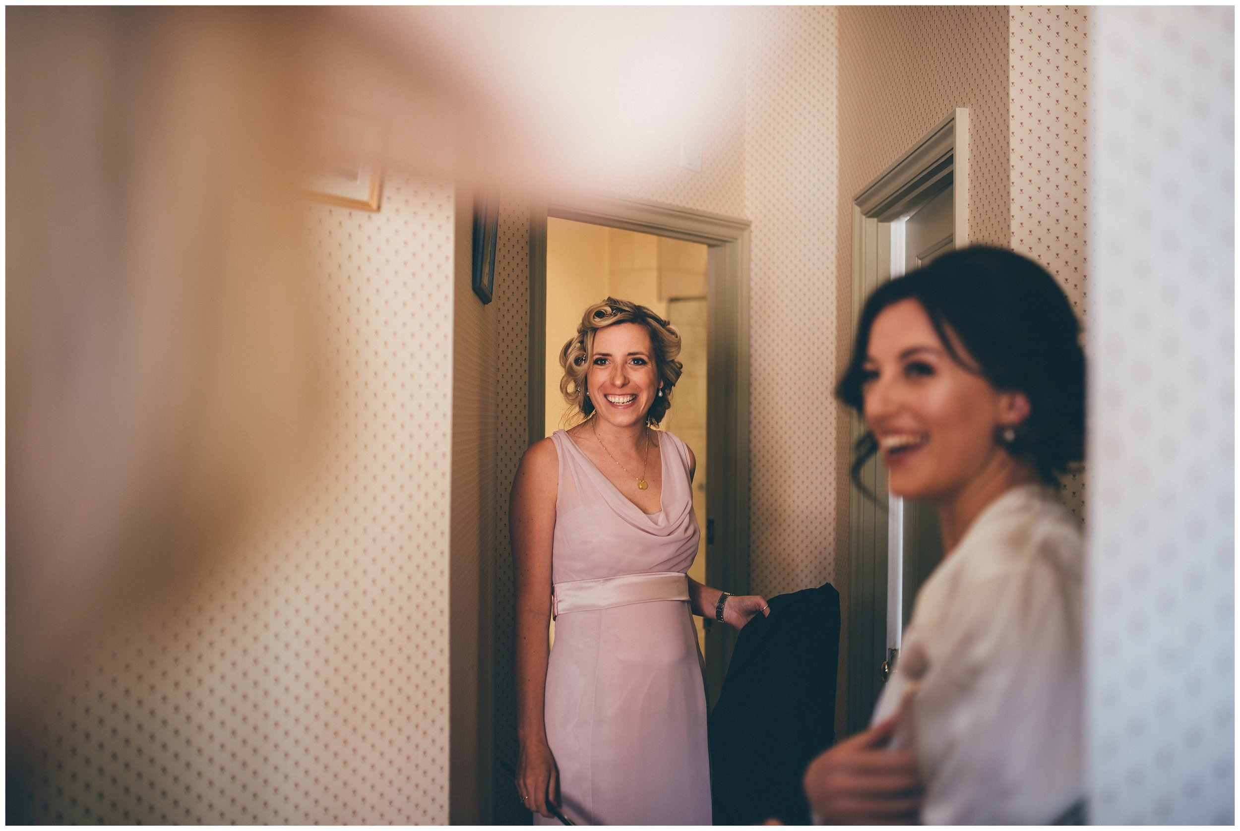 Bridesmaids dressed in dusky pink smile at the mother of the bride.